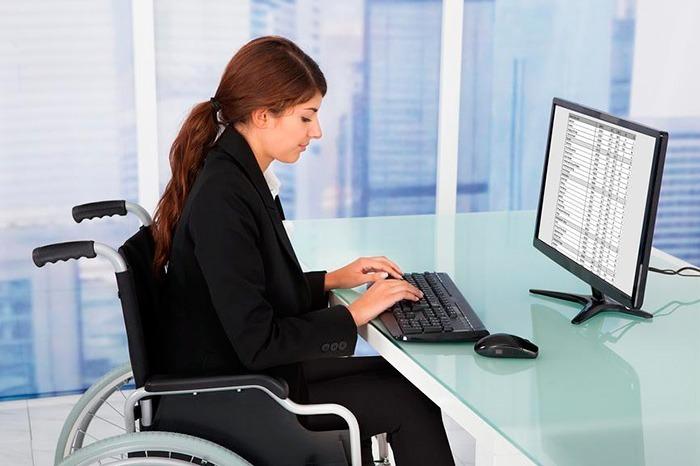 Девушка в инвалидном кресле работает за ПК