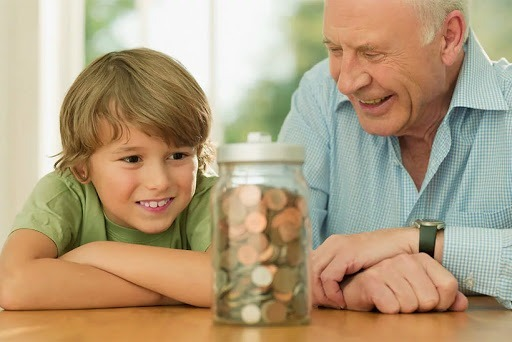 Дедушка и внук который смотрит на банку с мелочью